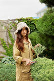 Girl gardener in working clothes and straw hat cuts garden scissoors evergreen Royalty Free Stock Image