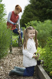 Girl Gardening With Mother In Field Stock Images