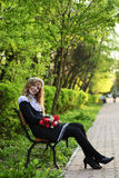 Girl in garland sit on behcn Royalty Free Stock Photos