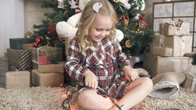 Girl with garland under the tree. The child is waiting for Christmas and New Year and put on flashing garland stock video