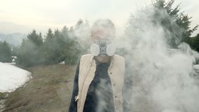Girl in gas mask looks straight through the smoke. In forest stock video footage