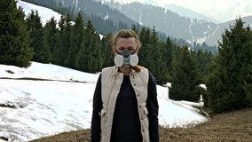 Girl in gas mask standing in nature and looking at the camera. In spring stock video footage