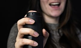 Girl with a gas, pepper spray, close-up, black background, protection stock photos