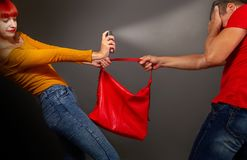 Girl gas robber. A girl defending pepper spray from a robber who is trying to take away her bag royalty free stock photos