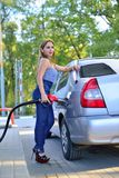 The girl runs the car at the gas station royalty free stock photography