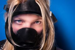 Girl in gasmask. Against blue wall Stock Photos