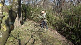 Girl gather cut branches in garden yard. Seasonal garden work . 4K. Young girl gather to pile cut dry branches in the garden yard. Seasonal garden work in early stock video