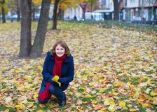 Girl gathering autumn leaves in park Royalty Free Stock Photo