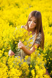 Girl gathers a bouquet of yellow wildflowers Royalty Free Stock Image