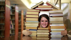Girl gazing through books stock video
