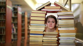 Girl gazing through books stock video footage