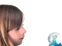 Girl gazing at globe. A girl gazing thoughtfully at a small globe containing a turtle, isolated on white Stock Photography