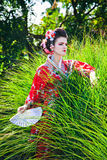Girl in geisha costume with a fan Royalty Free Stock Image