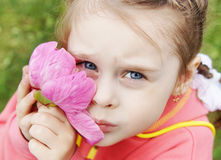 Girl gently presses to cheek a big pink flower Royalty Free Stock Images