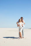 The girl gently touches her beloved`s face among the white sands Stock Image
