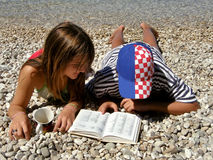 Girl from Germany and Croatian boy. Reading dictionary on the beach Royalty Free Stock Photos