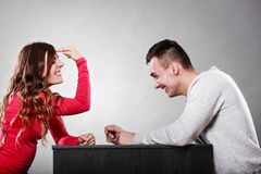 Girl gesturing with finger sitting in front of man Royalty Free Stock Photography