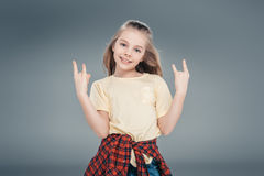 Girl gesturing rock sign. Smiling casual dressed girl gesturing rock sign isolated on gray Stock Image