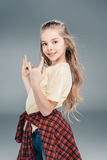 Girl gesturing rock sign. Smiling casual dressed girl gesturing rock sign isolated on gray Stock Photo