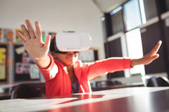 Girl gesturing while using virtual reality glasses in classroom. At school Royalty Free Stock Photo