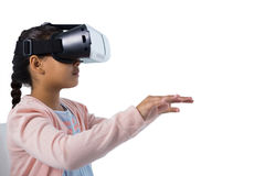 Girl gesturing while using virtual reality headset. Against white background Stock Image