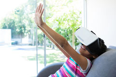 Girl gesturing while wearing virtual reality simulator at home. Side view of girl gesturing while wearing virtual reality simulator at home Royalty Free Stock Photography
