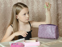 The girl gets a beads from a ladies' handbag Stock Photo