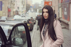 Girl gets into the car. She is dressed in a coat Stock Photo