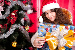 Girl gets a Christmas present. Girl gets a Christmas gift, decorated Christmas tree, red background, beautiful clothes Royalty Free Stock Photography
