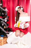 Girl gets a Christmas present. Girl gets a Christmas gift, decorated Christmas tree, red background, beautiful clothes Stock Photography