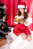 Girl gets a Christmas present. Girl gets a Christmas gift, decorated Christmas tree, red background, beautiful clothes Royalty Free Stock Photo