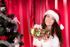 Girl gets a Christmas present. Girl gets a Christmas gift, decorated Christmas tree, red background, beautiful clothes Royalty Free Stock Image