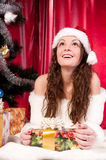 Girl gets a Christmas present. Girl gets a Christmas gift, decorated Christmas tree, red background, beautiful clothes Stock Photos