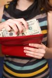 The girl gets dollars from a purse. Female hands get money from a purse Stock Photos