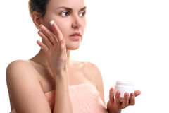 Girl gets a face cream Royalty Free Stock Photography