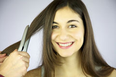 Girl gets her hair ironed smiling Royalty Free Stock Photography