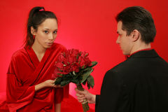 Girl gets roses. He hands her a bouquet of red roses to celebrate on red backround Royalty Free Stock Image