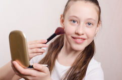 Girl gets twelve years brush powder on the face Royalty Free Stock Photo