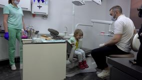 Girl gets up from the dental chair and says goodbye. To the doctor. Dental clinic stock footage