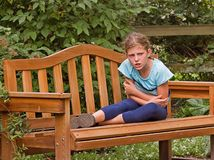 Girl Getting Angry on Park Bench. This girl is getting angry and about to throw a temper tantrum while sitting on this park bench outdoors Royalty Free Stock Image