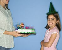 Girl getting birthday cake. Girl wearing party hat with mother holding birthday cake Royalty Free Stock Photography