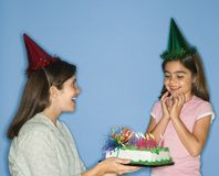 Girl getting birthday cake. Girl wearing party hat with mother holding birthday cake Royalty Free Stock Photo