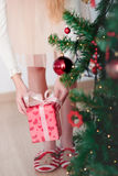 Girl getting Christmas gift from under a tree Stock Photography