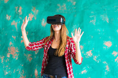Girl getting experience using VR-headset glasses of virtual reality gesticulating hands Royalty Free Stock Images