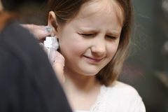 Girl getting her ears pierced. Young girl grimacing while getting her ears pierced Stock Photos