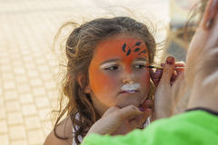 Girl getting her face painted by painting artist. Stock Photography