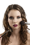Girl getting made-up with brushes on the face Royalty Free Stock Images