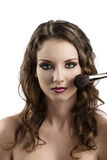 Girl getting made-up with brushes, she smiles Stock Photography