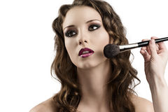 Girl getting made-up by hands with brushes Royalty Free Stock Photo