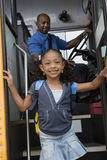 Girl Getting Off School Bus. Portrait of a cute little girl getting off the school bus stock image
